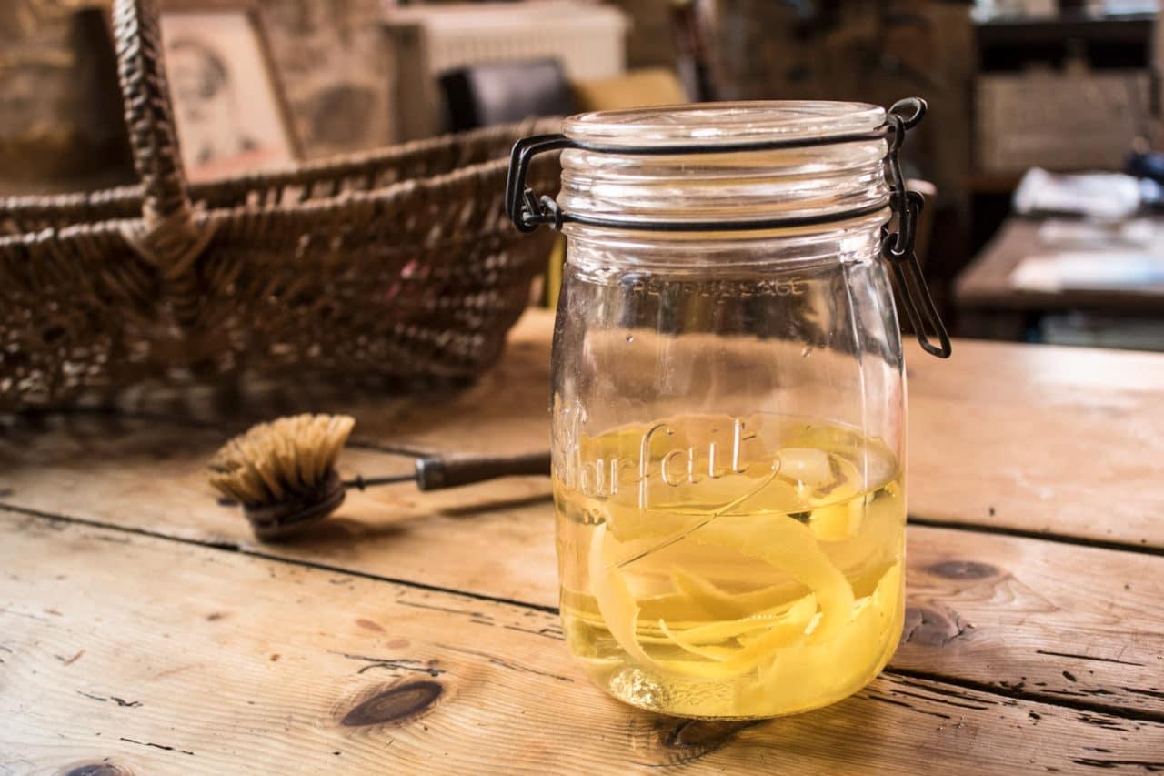 Bocal en verre avec vinaigre blanc et écorces de citron